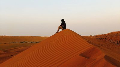 Gilman recipient Tahreem Alam sits atop a dune in the Ash-Sharqiyah desert of Oman.